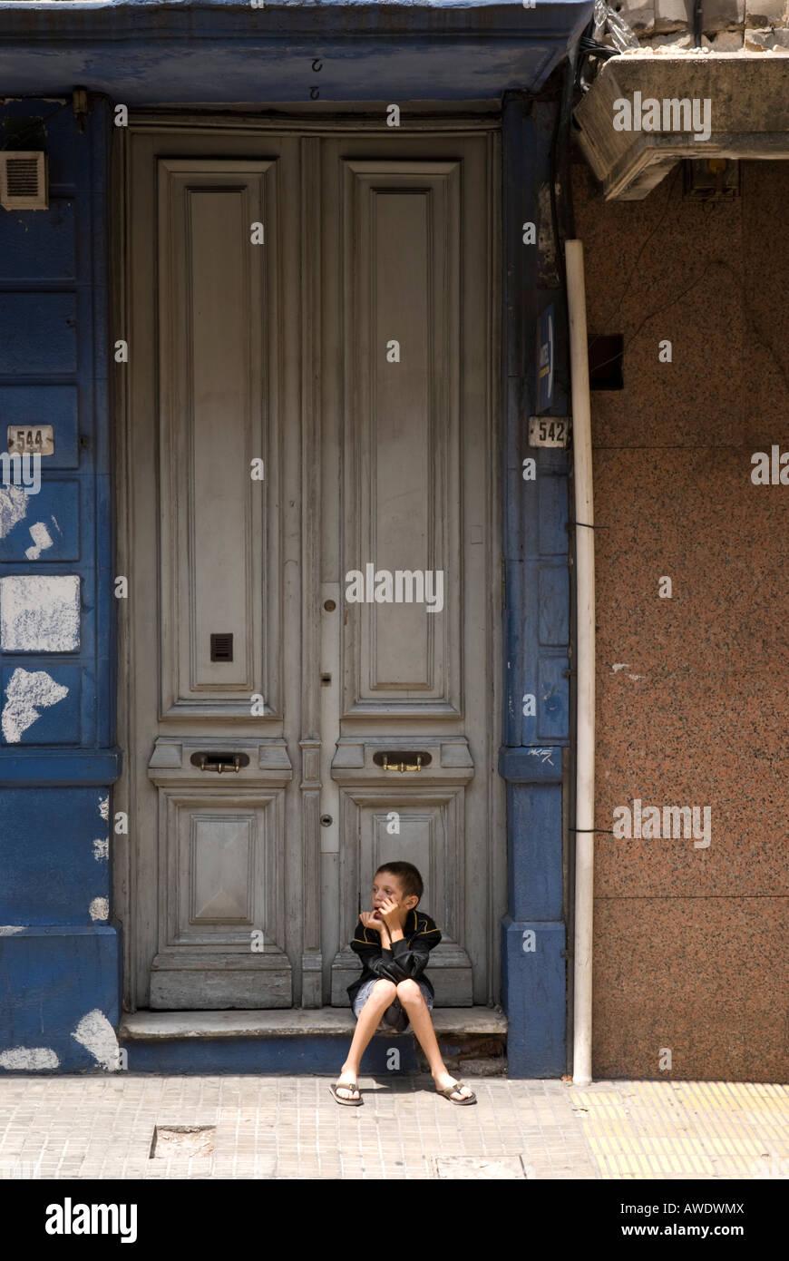 Street kid sitting by door in Montevideo, Uruguay - Stock Image