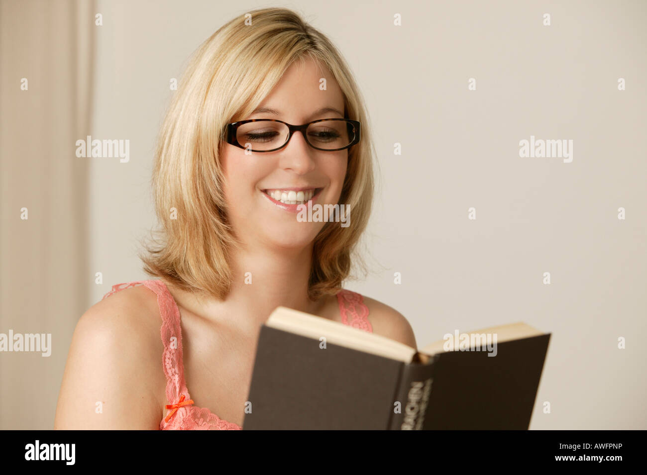 young blonde woman wearing glasses reading a book stock photo
