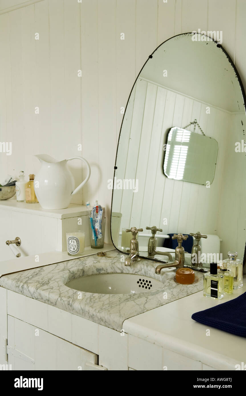 Mirror and marbled washbasin in bathroom of London townhouse - Stock Image