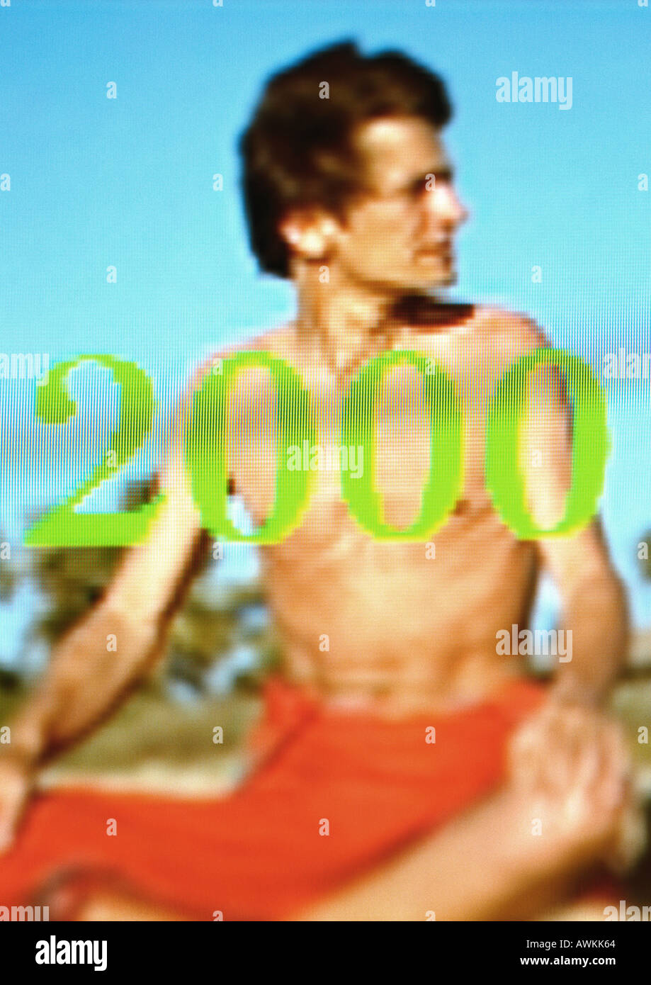 Man on beach in loincloth, '2000' - Stock Image