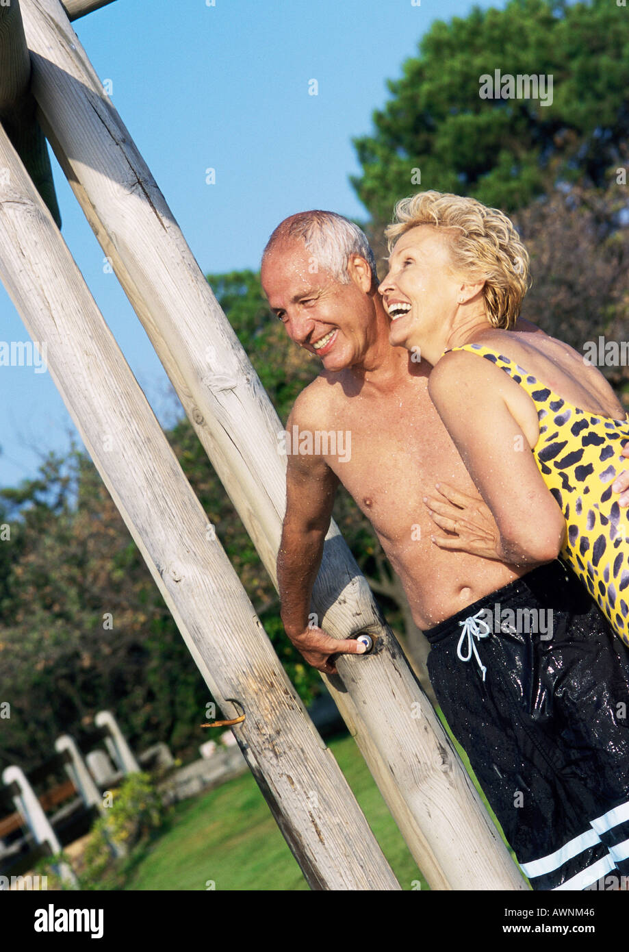 mature man and woman standing in bathing suits in outdoor shower
