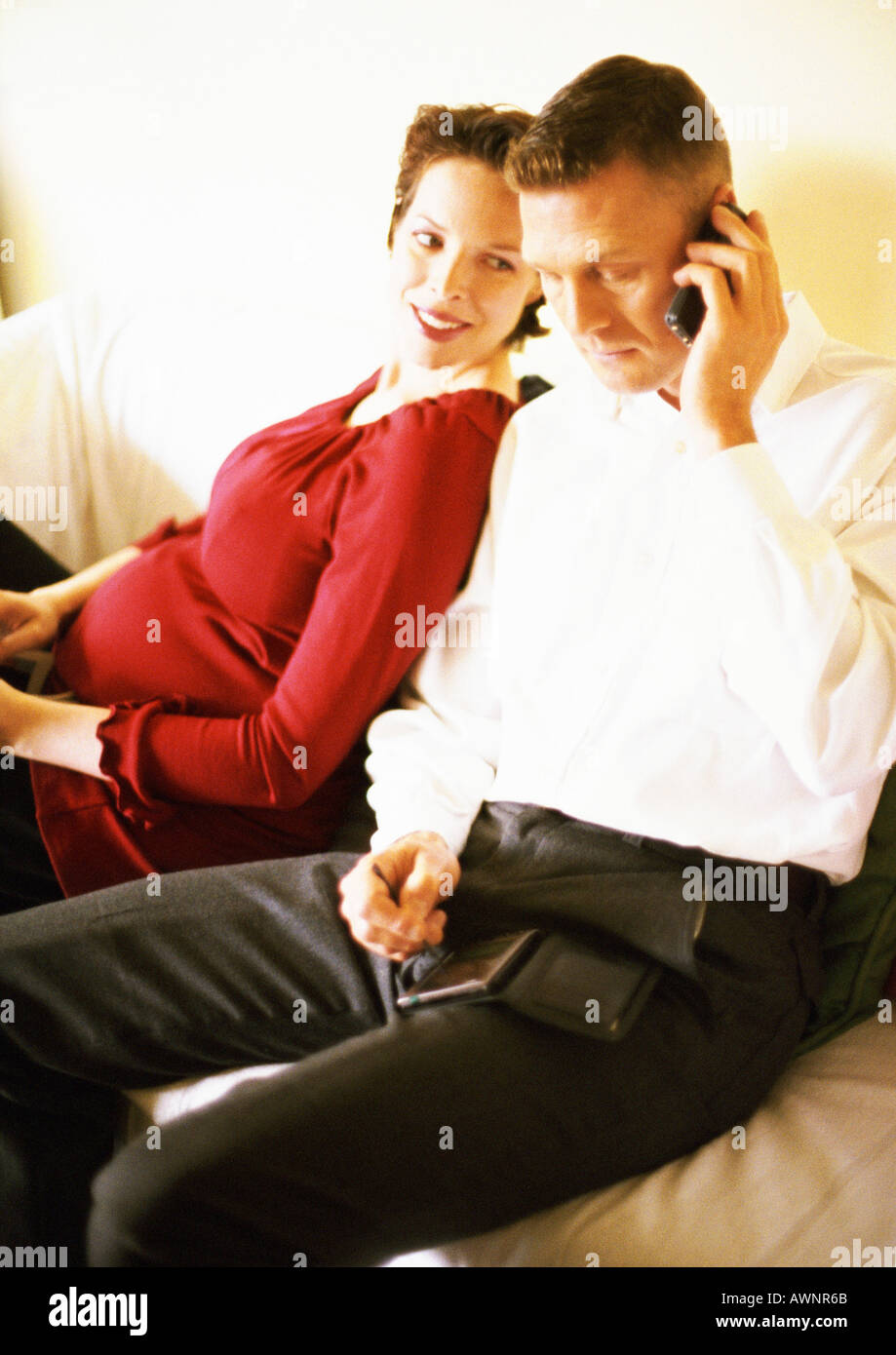 Pregnant woman leaning against man talking on cell phone - Stock Image