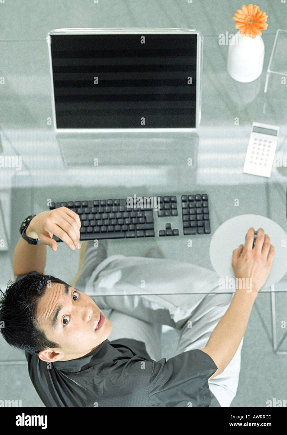 Man at desk with futuristic devices, high angle view, portrait - Stock Image