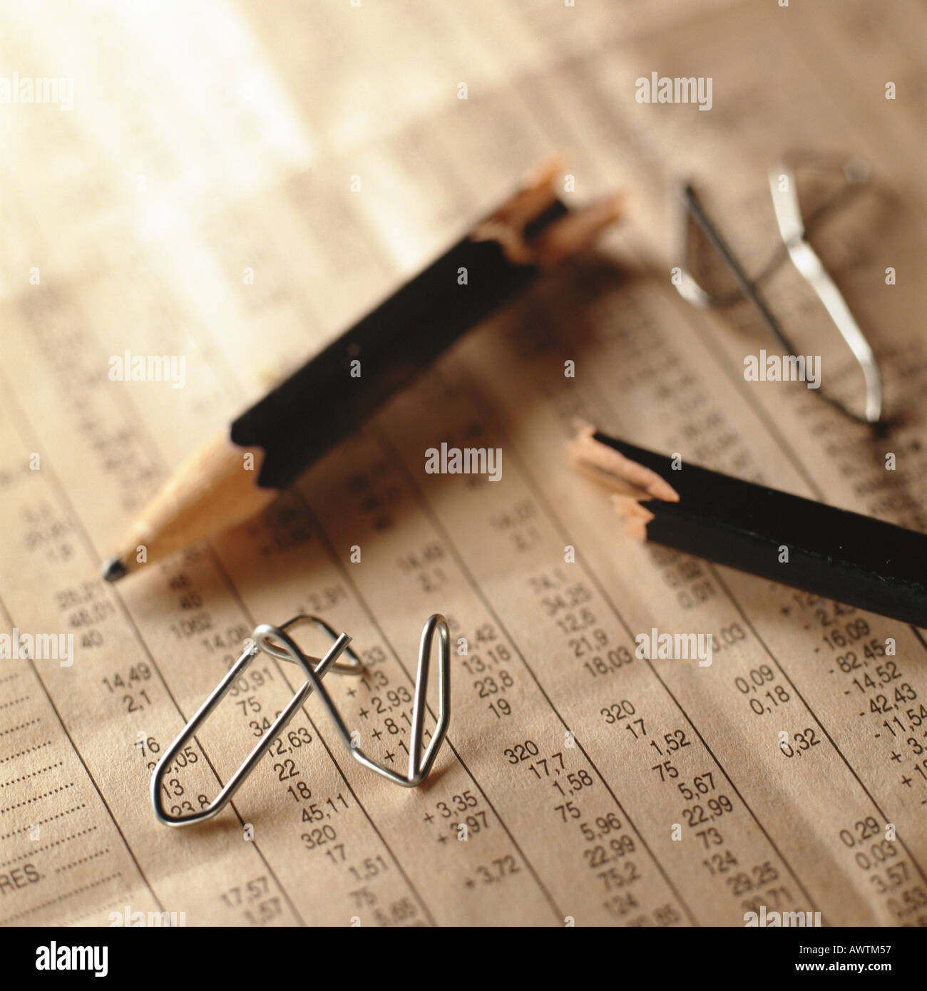 Broken pencil and twisted paper clips on top of financial numbers - Stock Image