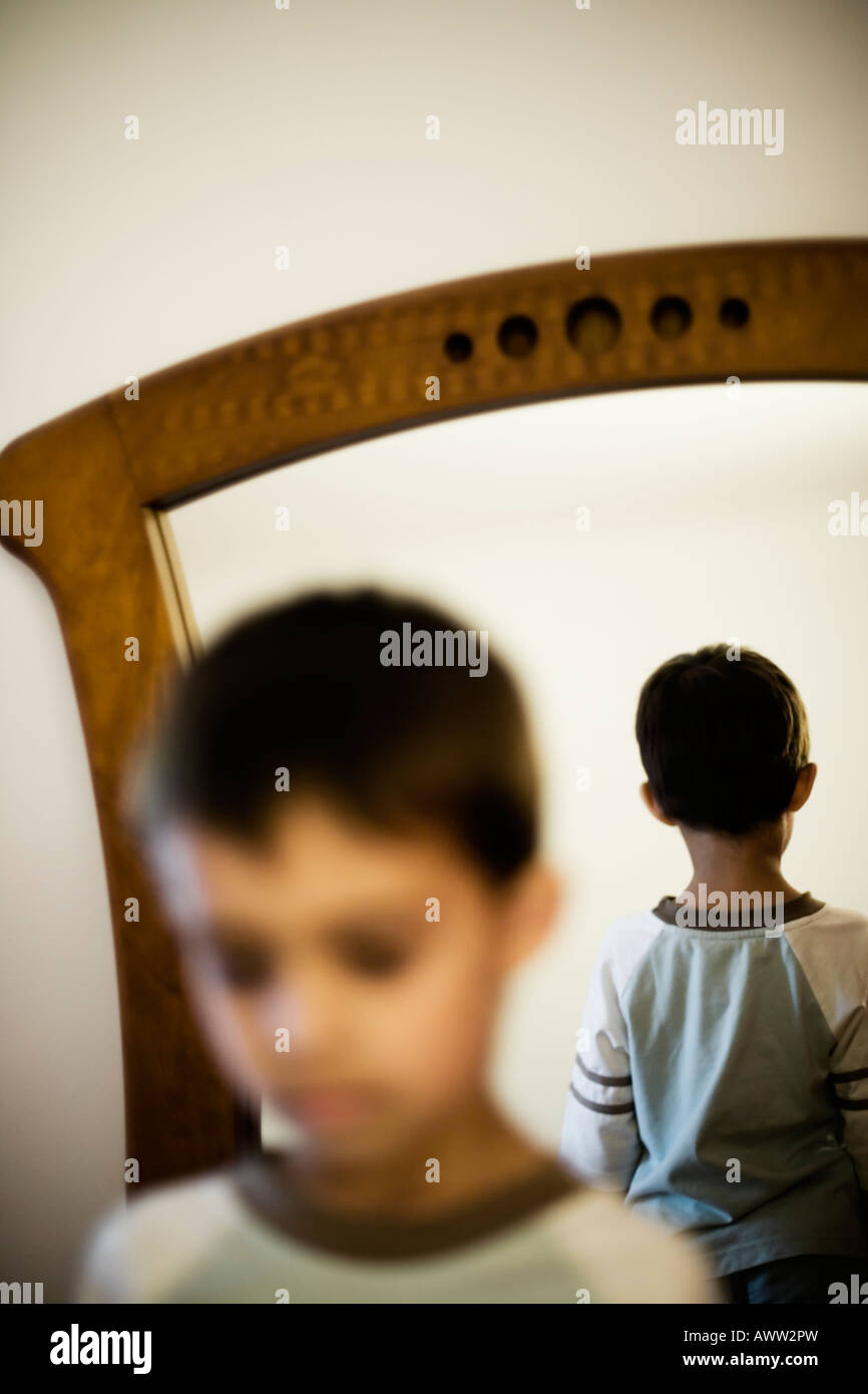 Face with back of head reflected in a mirror - Stock Image