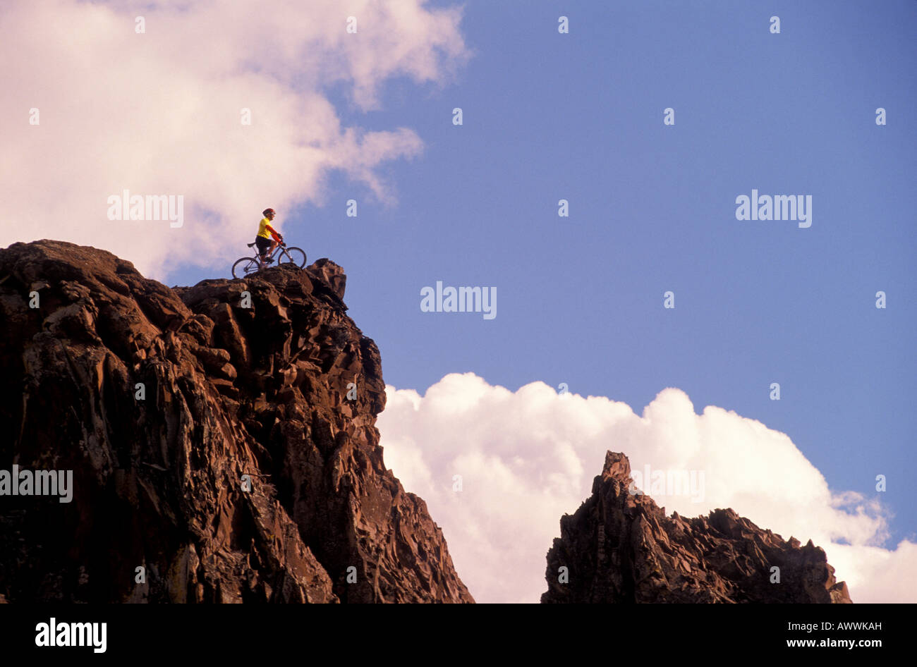 A mountain biker surveys the view as he pauses on a rocky crag in central Washington State - Stock Image