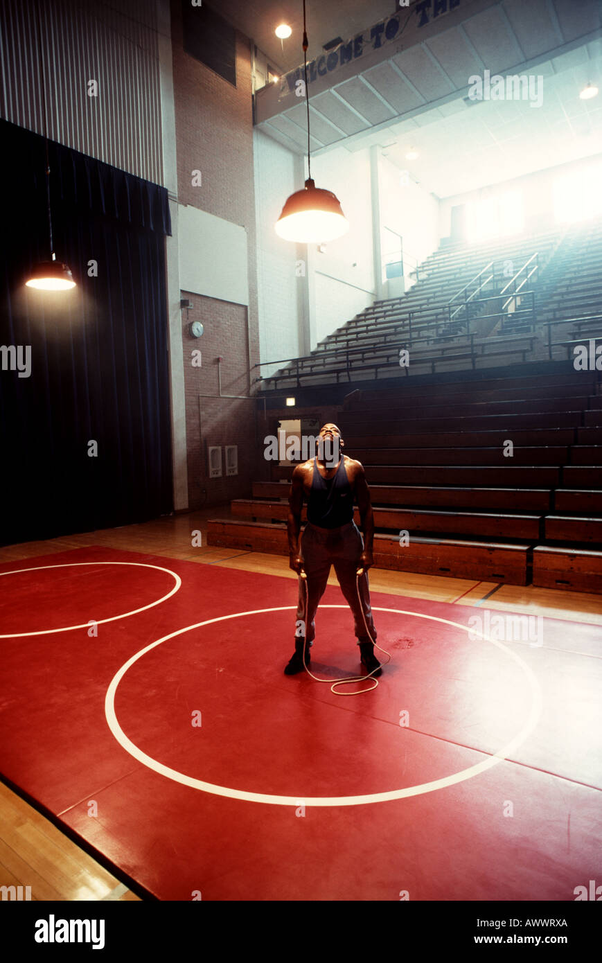 Portrait of a tired African American male athlete in a black tank & shorts with a jump rope in a retro gym under - Stock Image