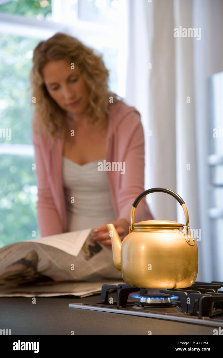 A woman reading the newspaper while waiting for a kettle to boil - Stock Image
