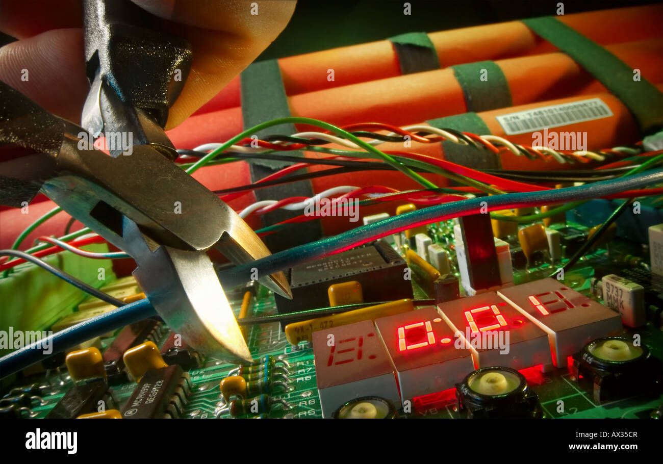Time bomb displaying numbers 0:01 and hand about to cut blue wire - Stock Image