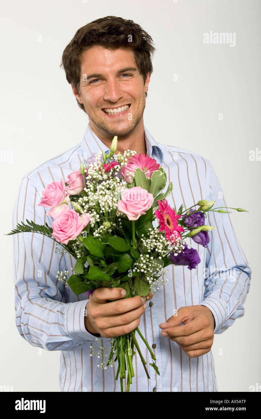 Young man holding bouquet of flowers smiling close up portrait young man holding bouquet of flowers smiling close up portrait izmirmasajfo Image collections