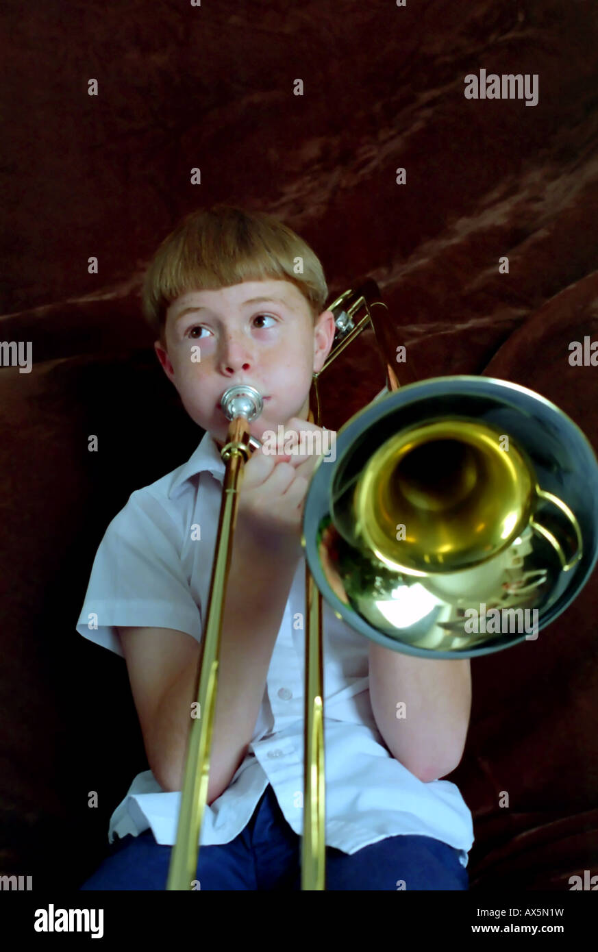 An 11 year old boy playing, or trying to play, the trombone. The musical instrument is almost bigger than he is. Stock Photo