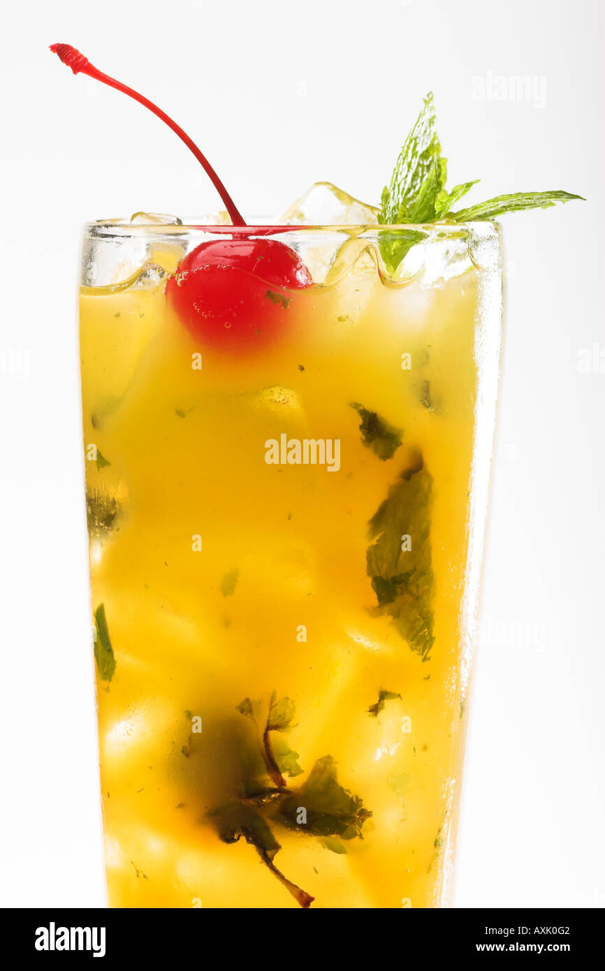 tropical yellow pineapple drink in glass with cheery leaves mint ice cold refreshing sweet tea juice moisture delicious - Stock Image