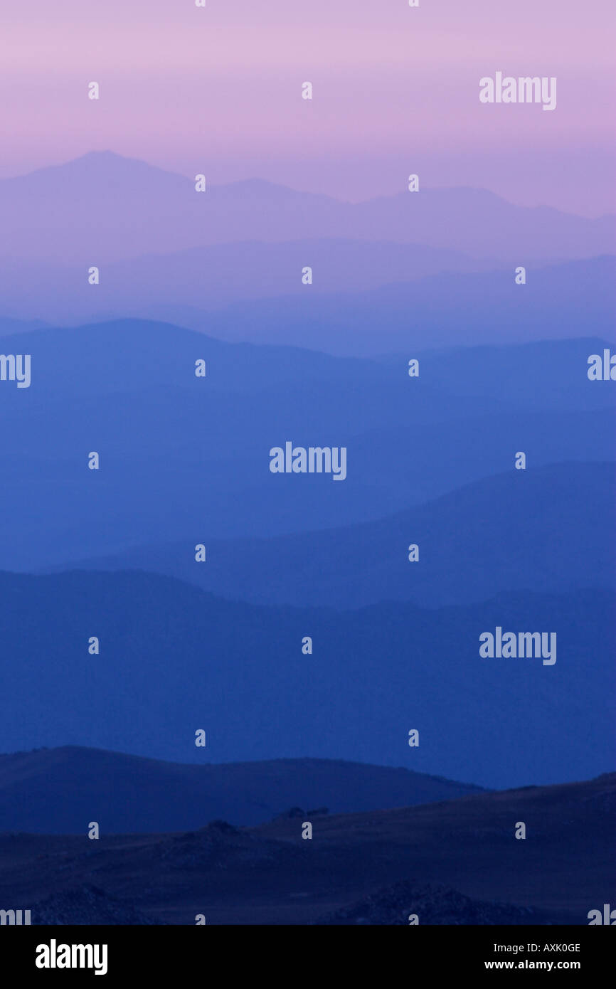 dark to light layers blue pink rolling wavy hill mountains in nature haze free ground earth color tones tall high - Stock Image