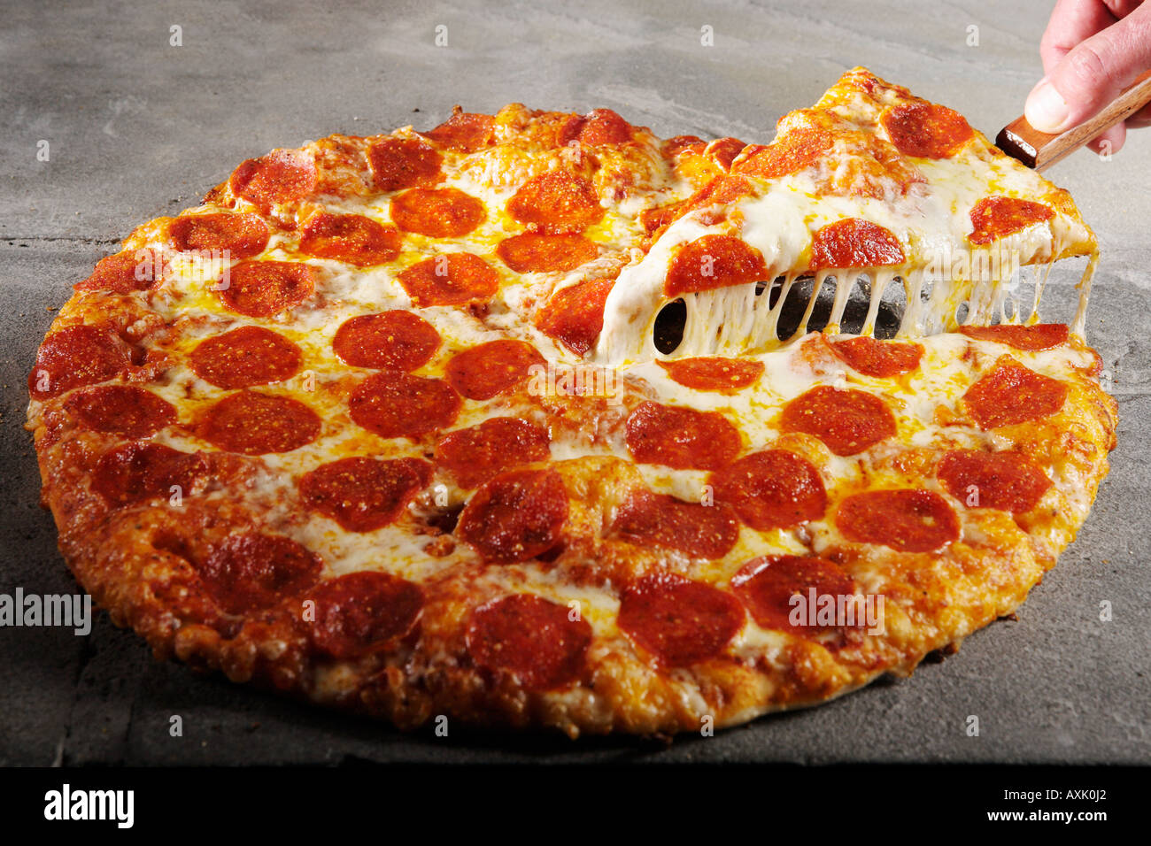 meat pepperoni pizza hand holding slice piece on spatula lifting up warm cheese bread crust on stone table round - Stock Image