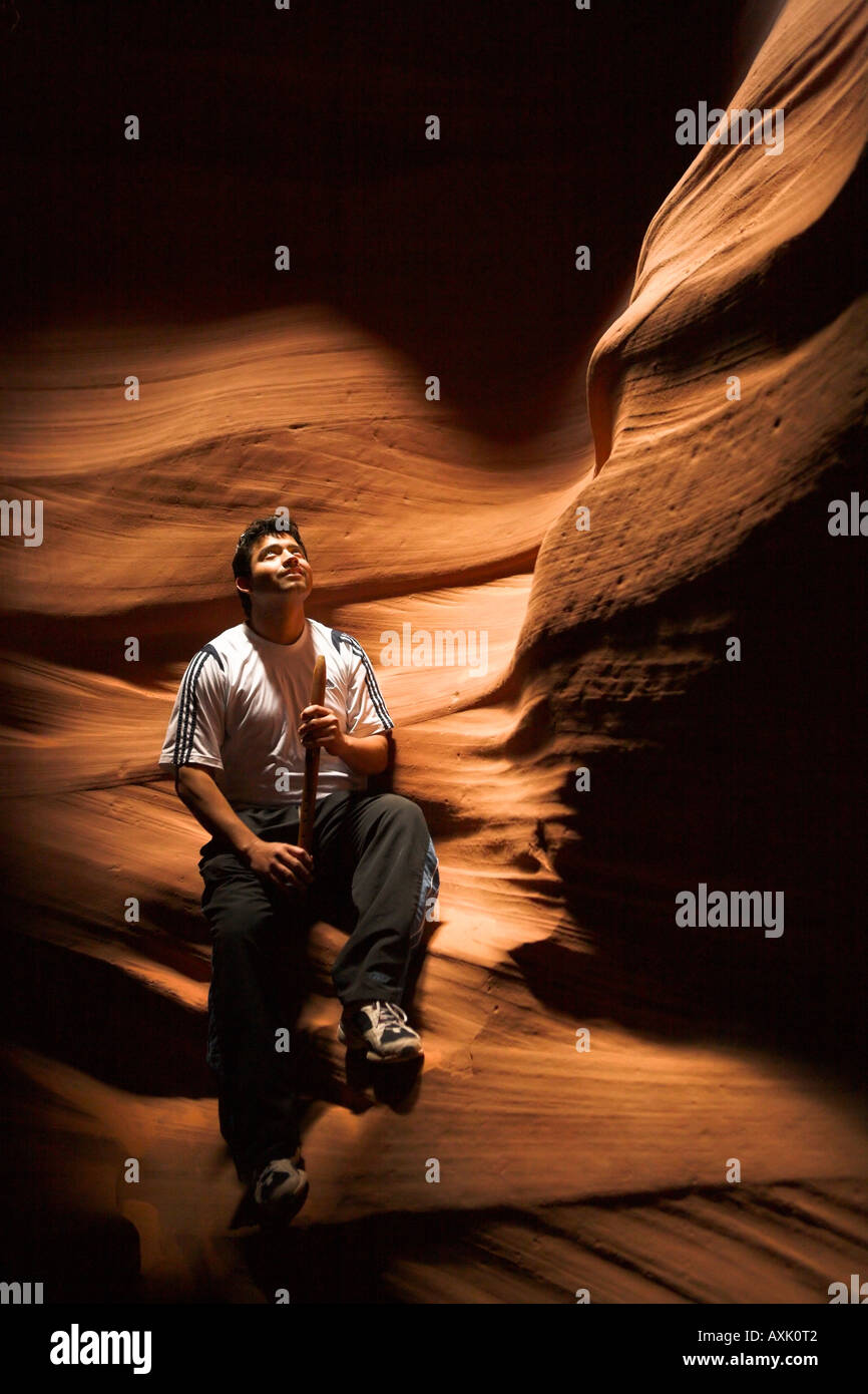 man person sitting listening in light on rock with whistle shadows dark white feel shoes body peace nature adventure - Stock Image