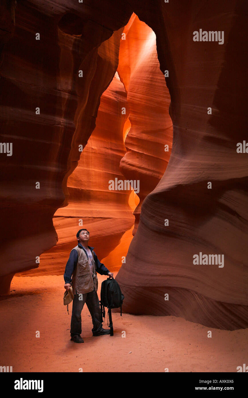 man person standing looking up tall long high rock wall canyon orange dirt rock gravel smooth adventure holding - Stock Image