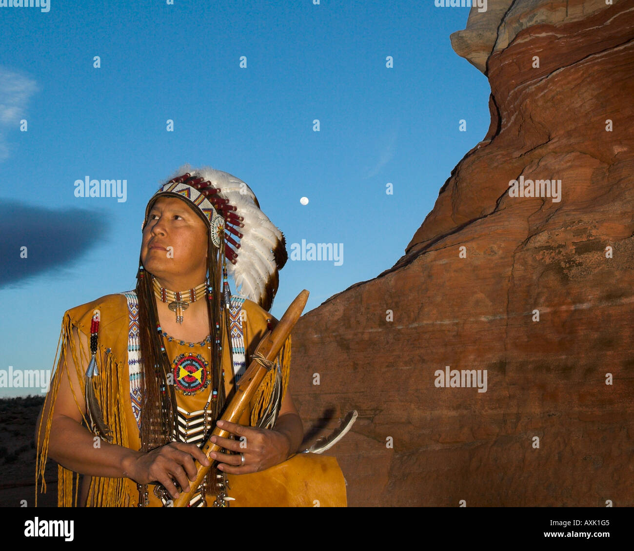 Native American Indian man person cultural outfit uniform headdress feathers hill patterns rock Chief nature beads - Stock Image