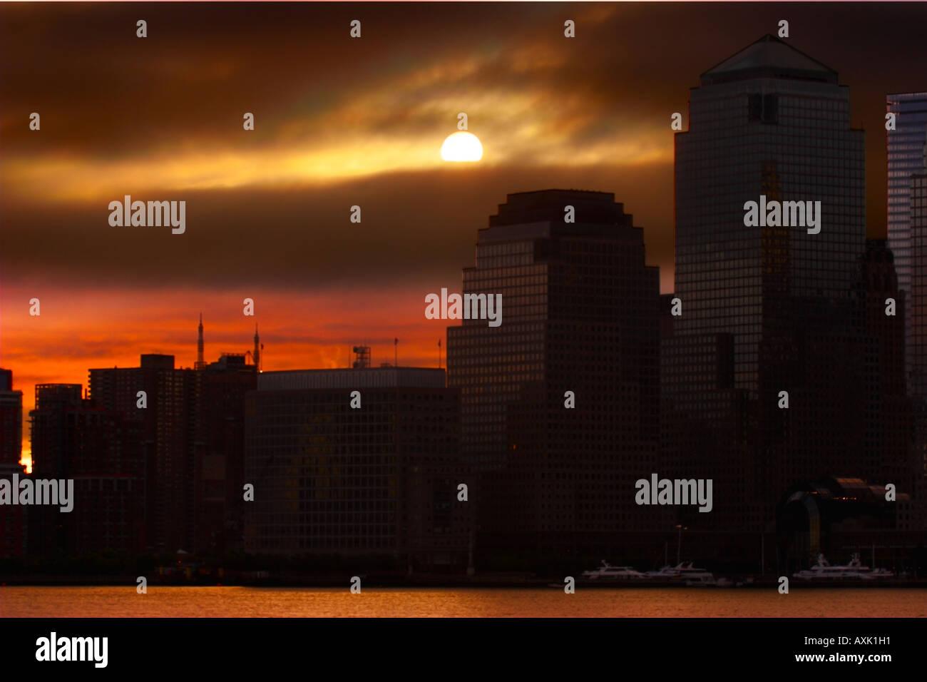 urban city sky clouds sun dusk sunset sunrise evening morning orange black shadow end water boats building city - Stock Image