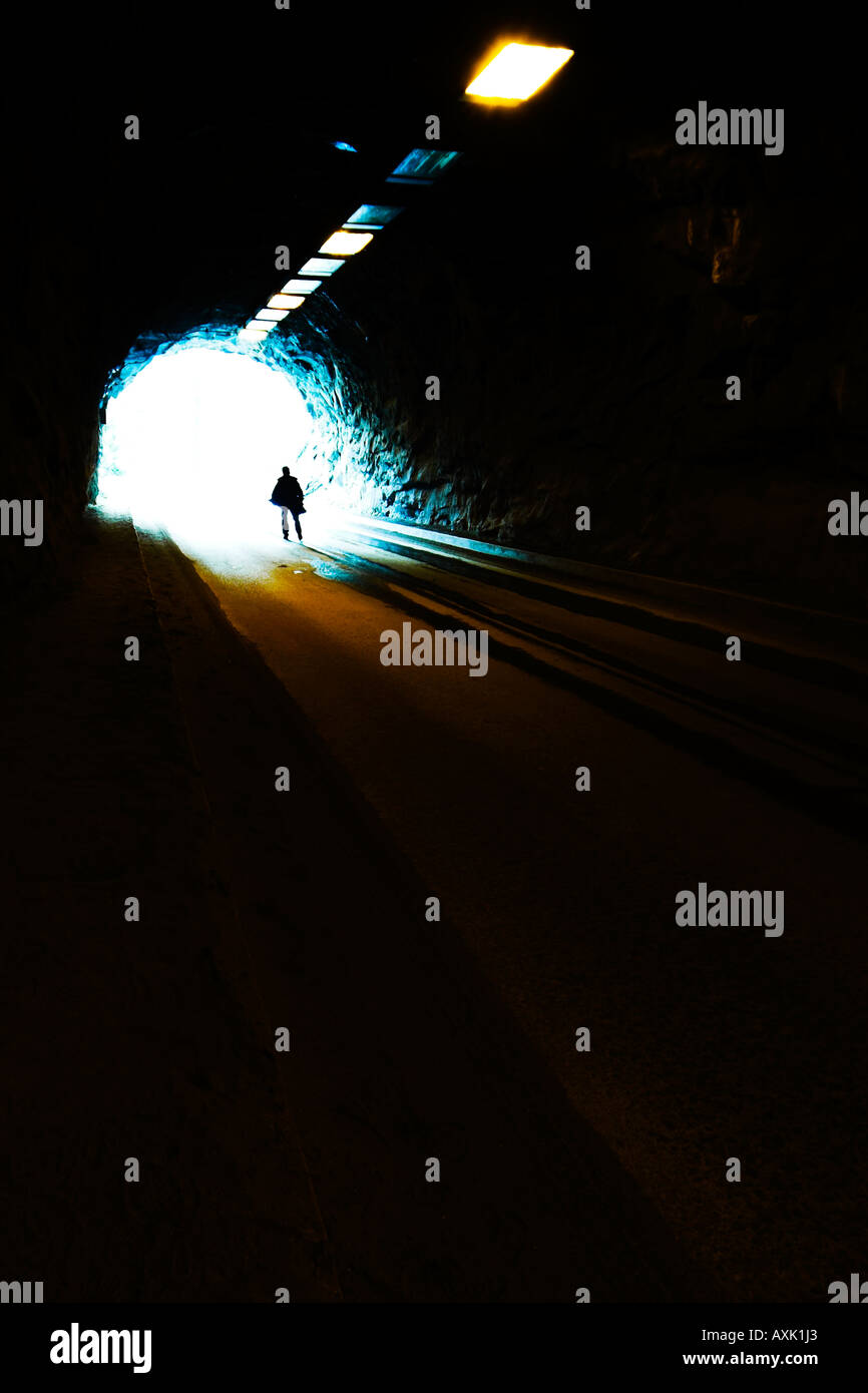 man person standing end railway tunnel sun day light ceiling circle blue brown black dark godly life death train - Stock Image