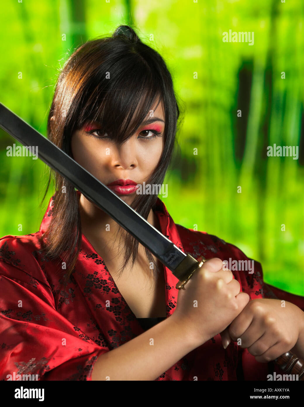 Asian tough fighting warrior girl holding sword diagonally with hair in eyes wearing red green background - Stock Image