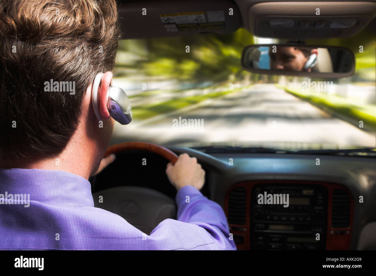 man person hair head shirt ear phone driving holding steering wheel talking speeding moving down road path rearview - Stock Image