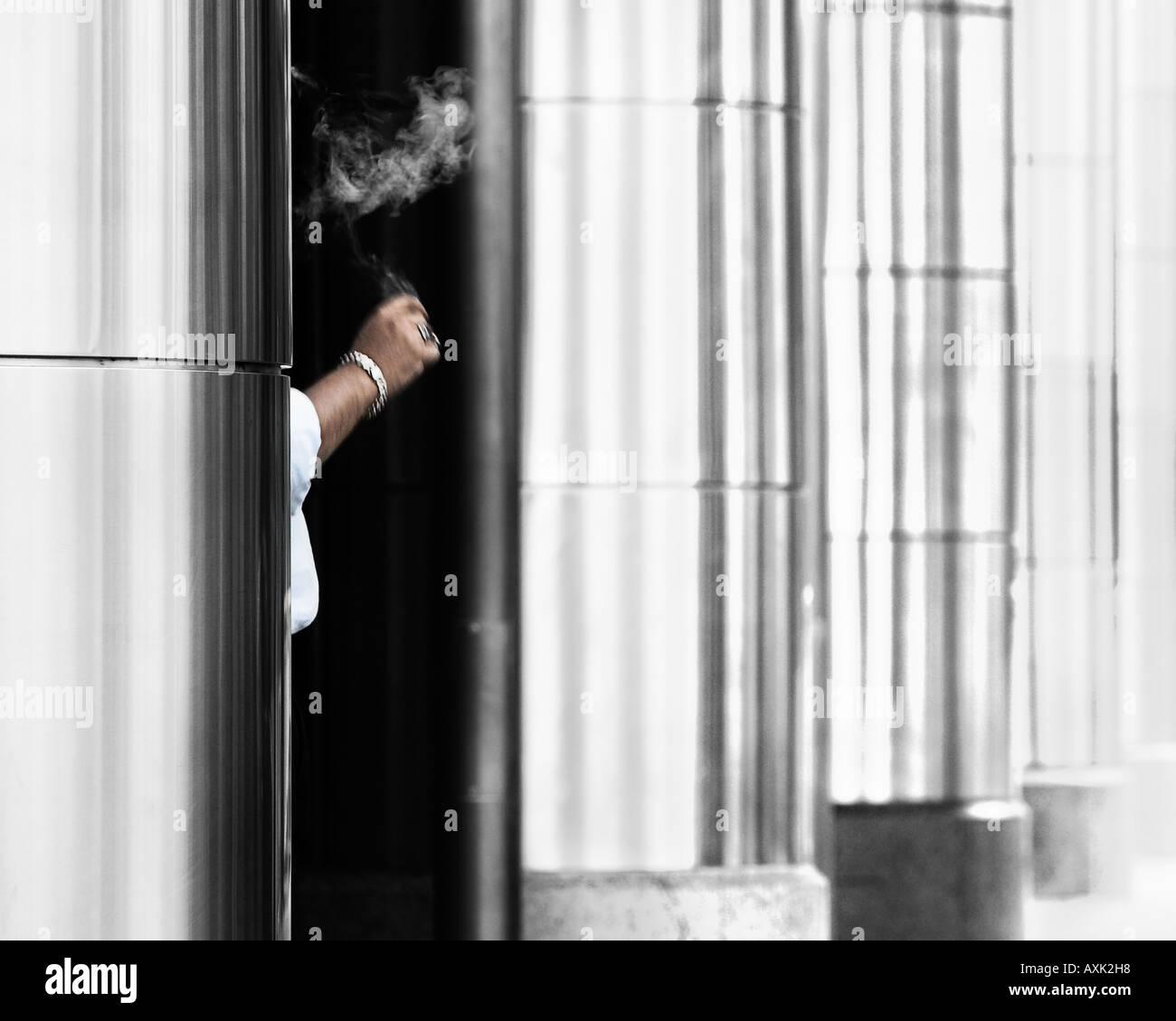 had arm bracelet hold hide smoke cigarette pillars lines white black doorway - Stock Image