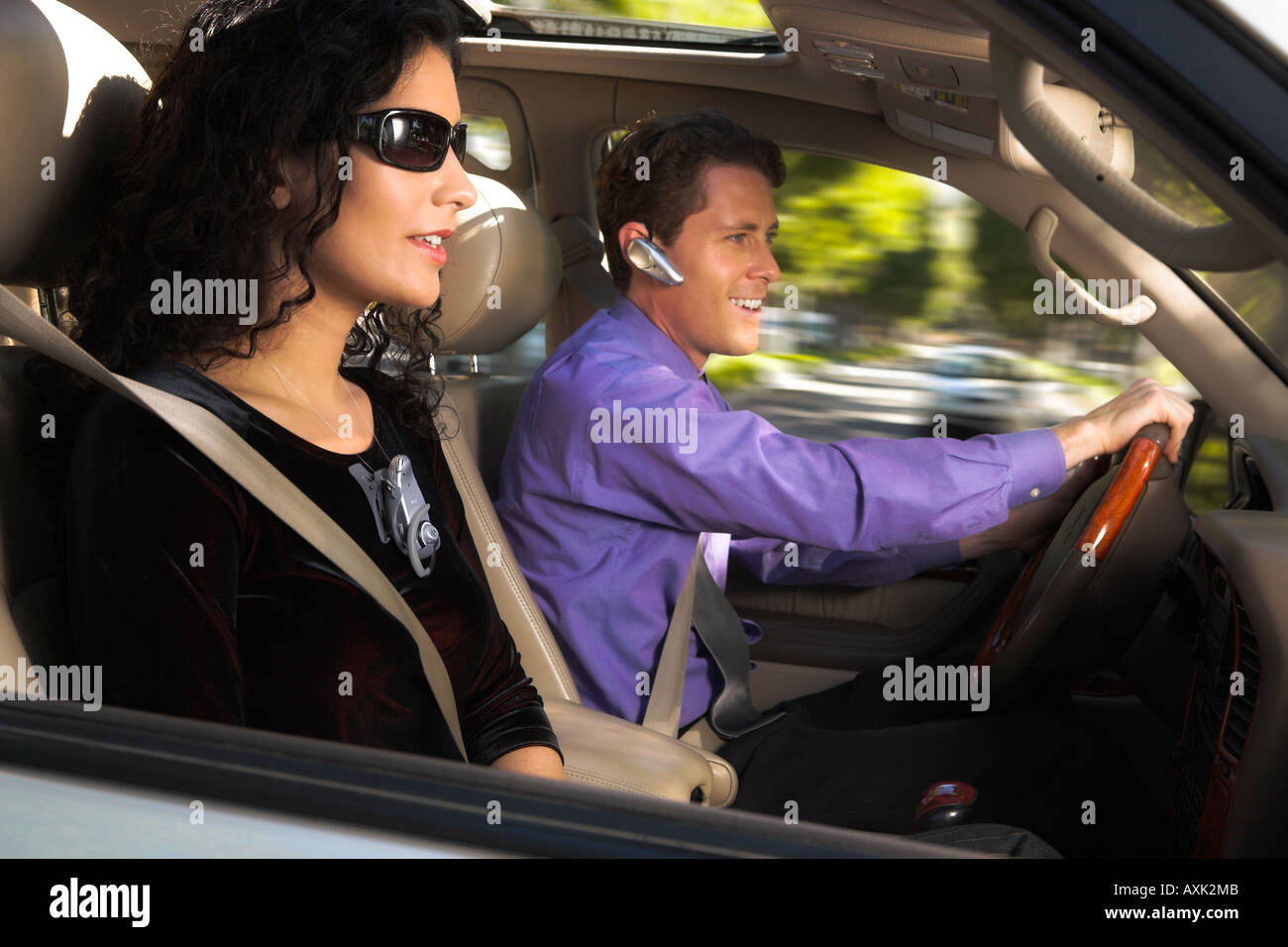 man male lady woman female partners work career driving car steering sheel seatbelt safety sunglasses movement phone - Stock Image