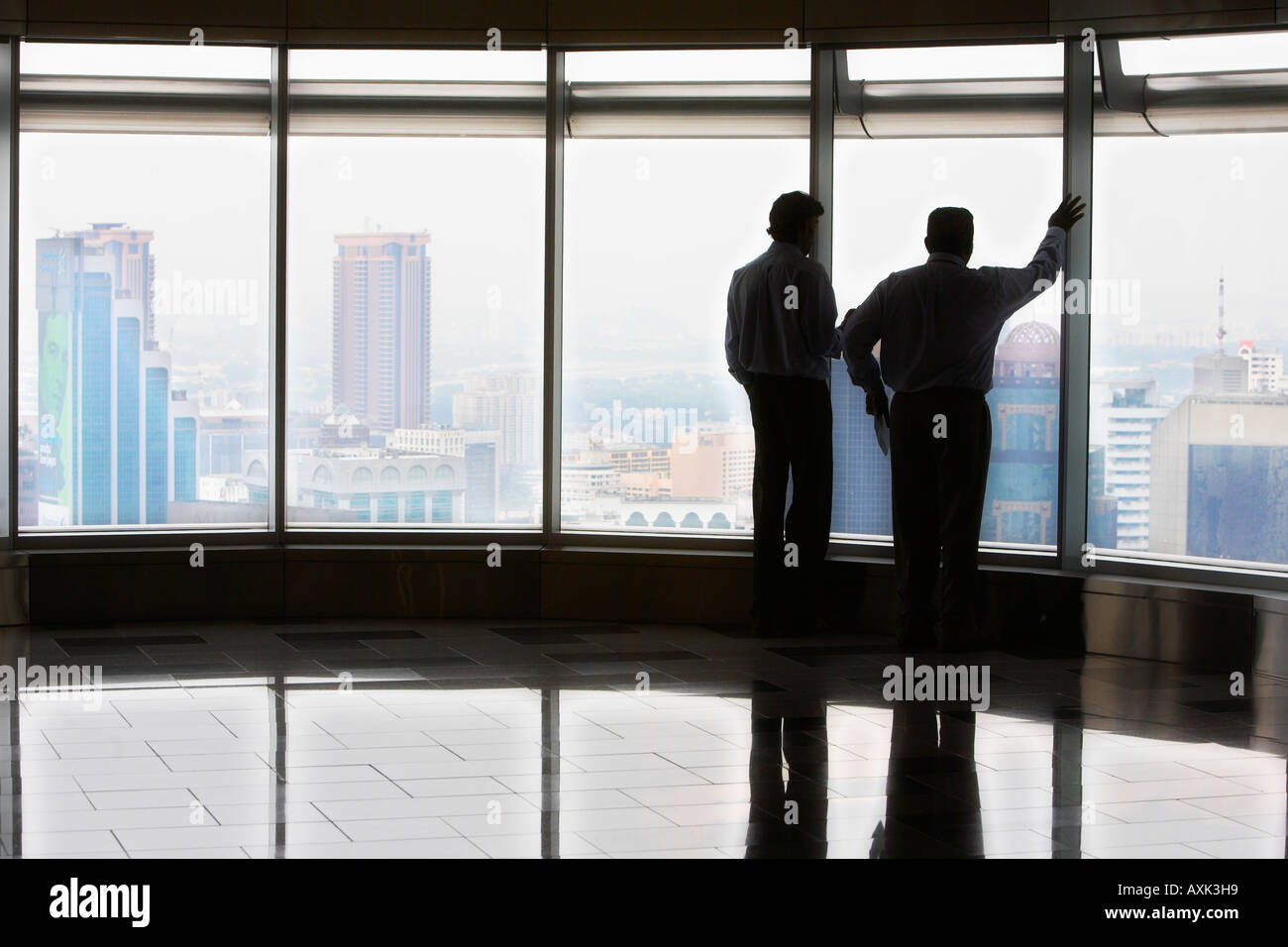 business working stand men male in new city skyscraper building windowns new office reflection floor looking distance - Stock Image