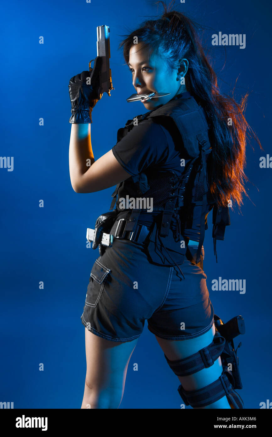Asian sexy girl woman lady fighting tough determined long hair focus aim back shoot gun gear straps glove knife - Stock Image