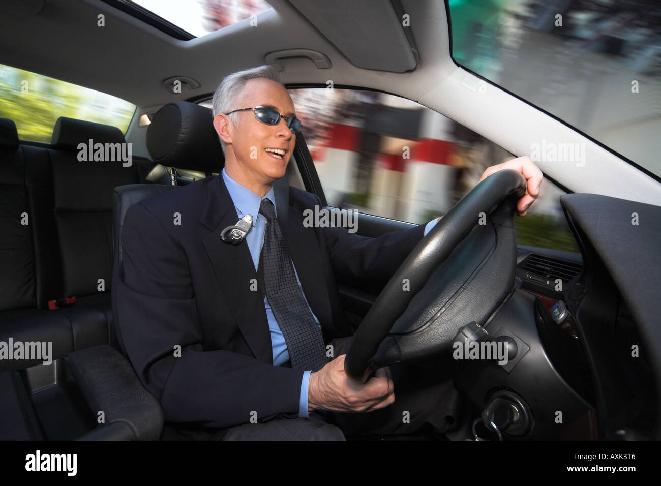 business work job career old elderly man sitting driving steering fast happy in new car holding wheel sunroof sunglasses - Stock Image