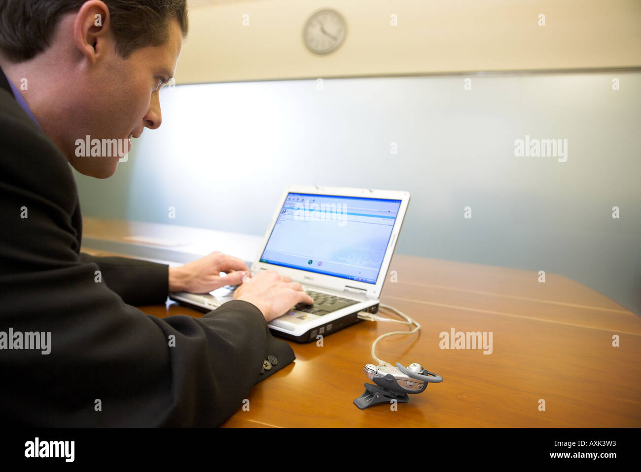 business man male working laptop technology work clock time fast desk table brown white silver grey day type touch - Stock Image