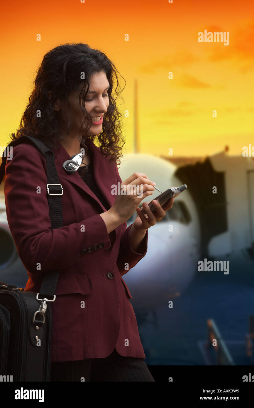 girl woman lady person with palm pilot touch screen business bag technology airplane fly trip work protable communnication - Stock Image