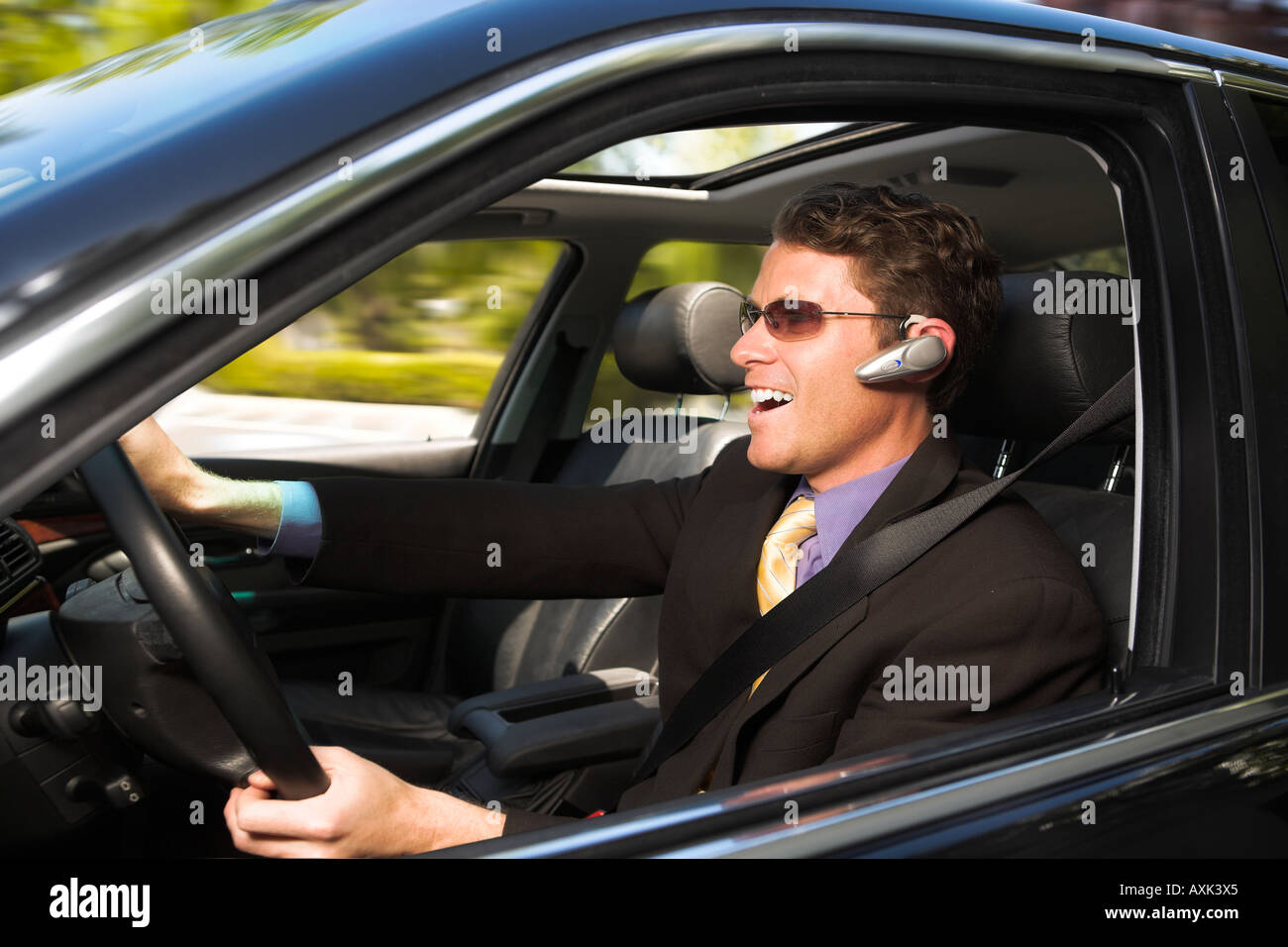business man person drive fast on phone hands on wheel safety movement go transport travel black yellow purble blue - Stock Image