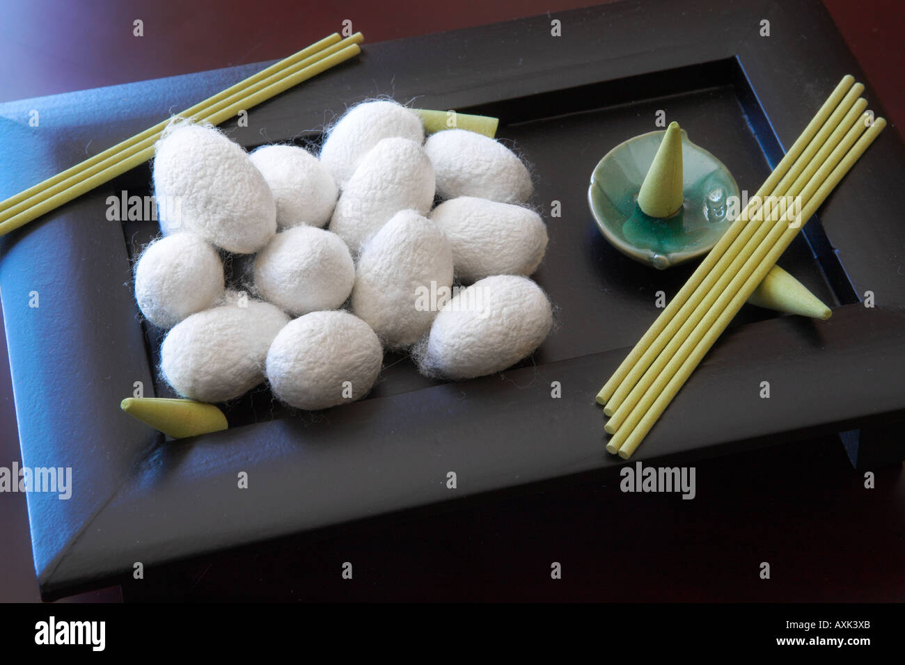 silk worm cocoon white green gormet food foreign white fuzz puff stick wood dish tray plate low stand eat consumption - Stock Image