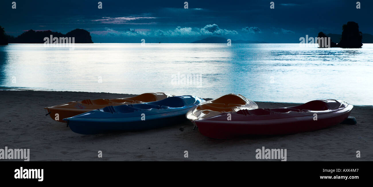 canoes boats beach bank water shore land wait surise sunset evening morning sky clouds orange blue pink red - Stock Image