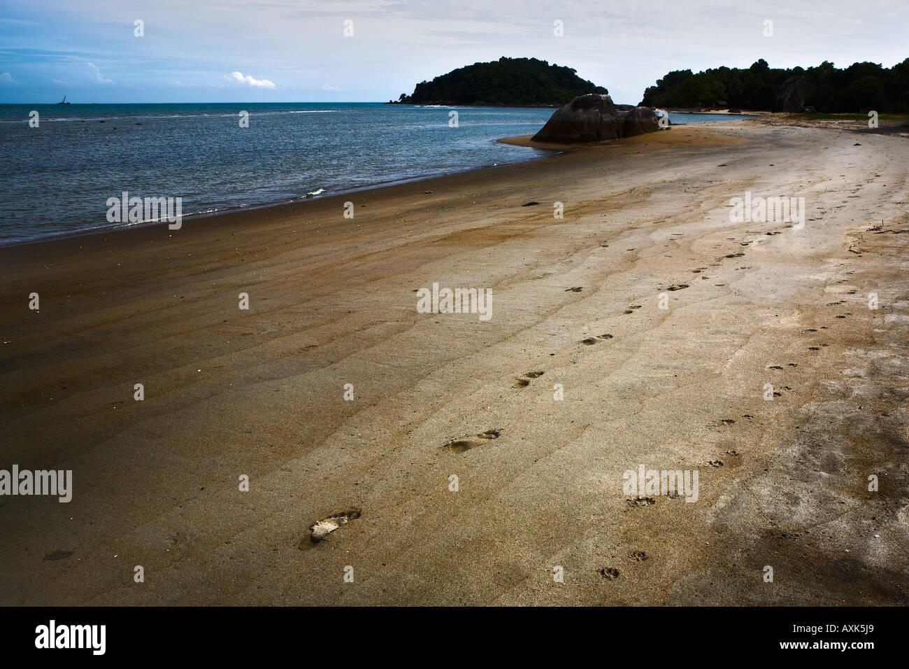 ocean water beach bank land footprints in sand rocks waves sky clouds - Stock Image