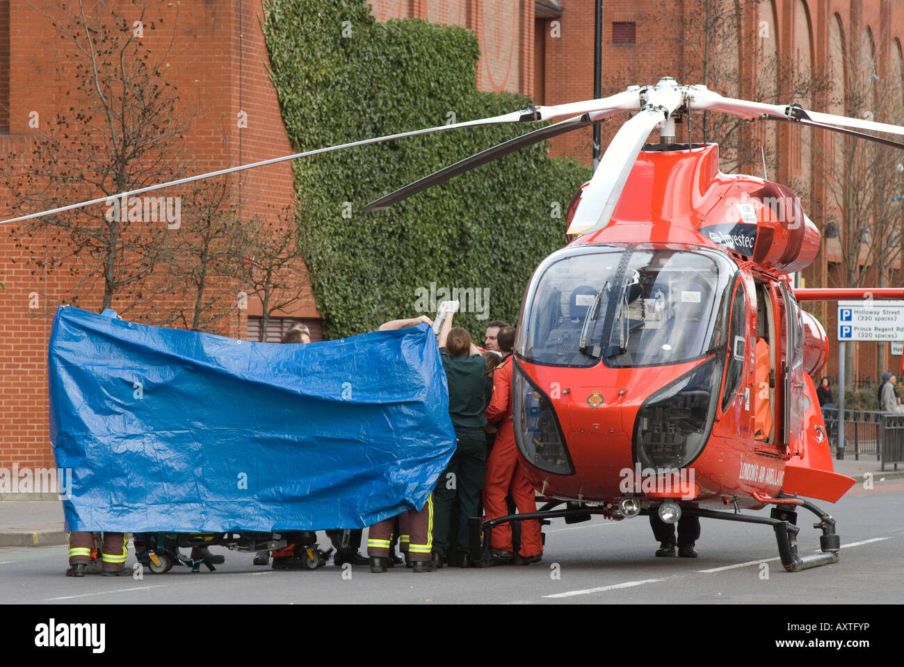 Emergency services personnel preparing road traffic accident victim for transportation by air ambulance - Stock Image
