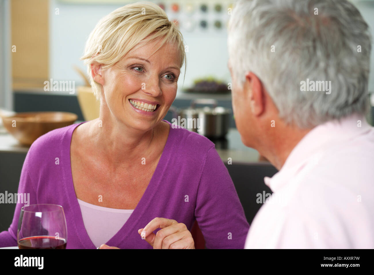 Blonde woman and gray-haired man having dinner, close-up, selective focus - Stock Image