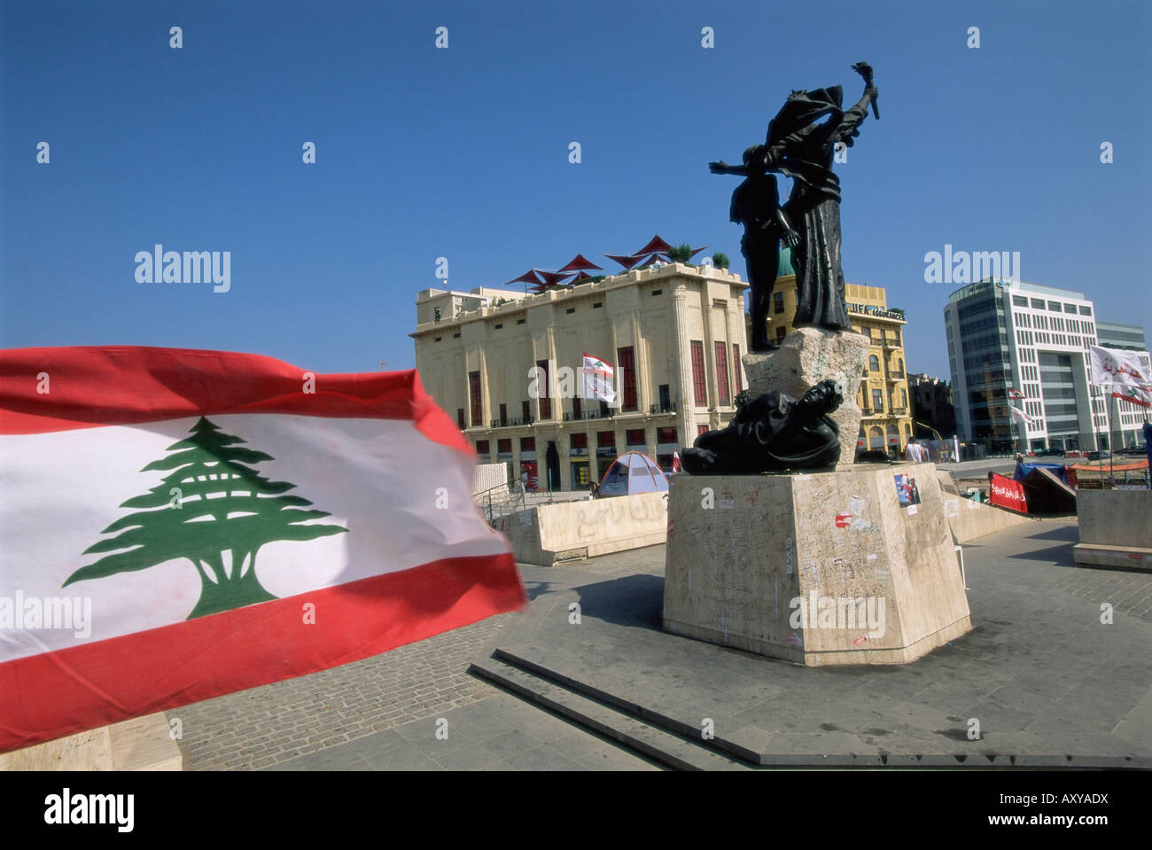 Lebanese flag and the Martyrs statue in the BCD, Place des Martyrs in the reconstructed city, Beirut, Lebanon, Middle - Stock Image
