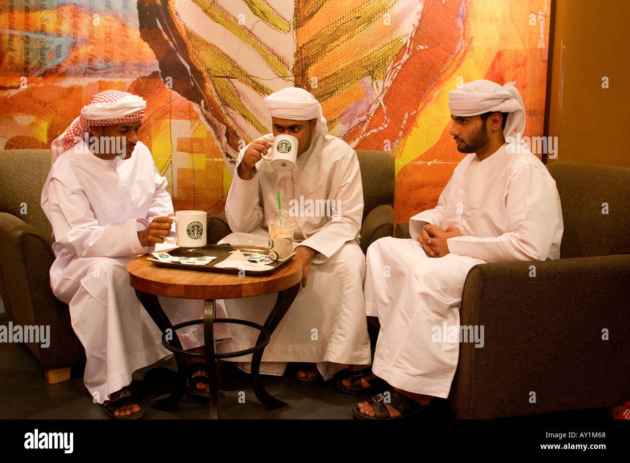 Young arab men with traditional dress sitting at starbucks cafe in Deira city centre shopping mall Dubai United - Stock Image