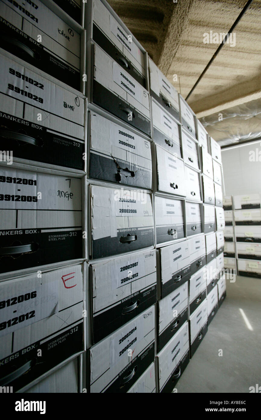 Files of paperwork stored in boxes in office building storage facility - Stock Image