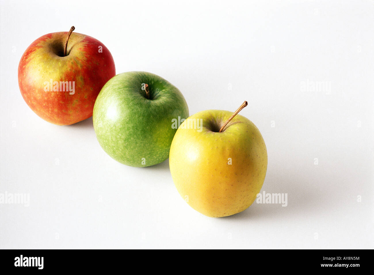 Three assorted apples in a diagonal row, close-up - Stock Image