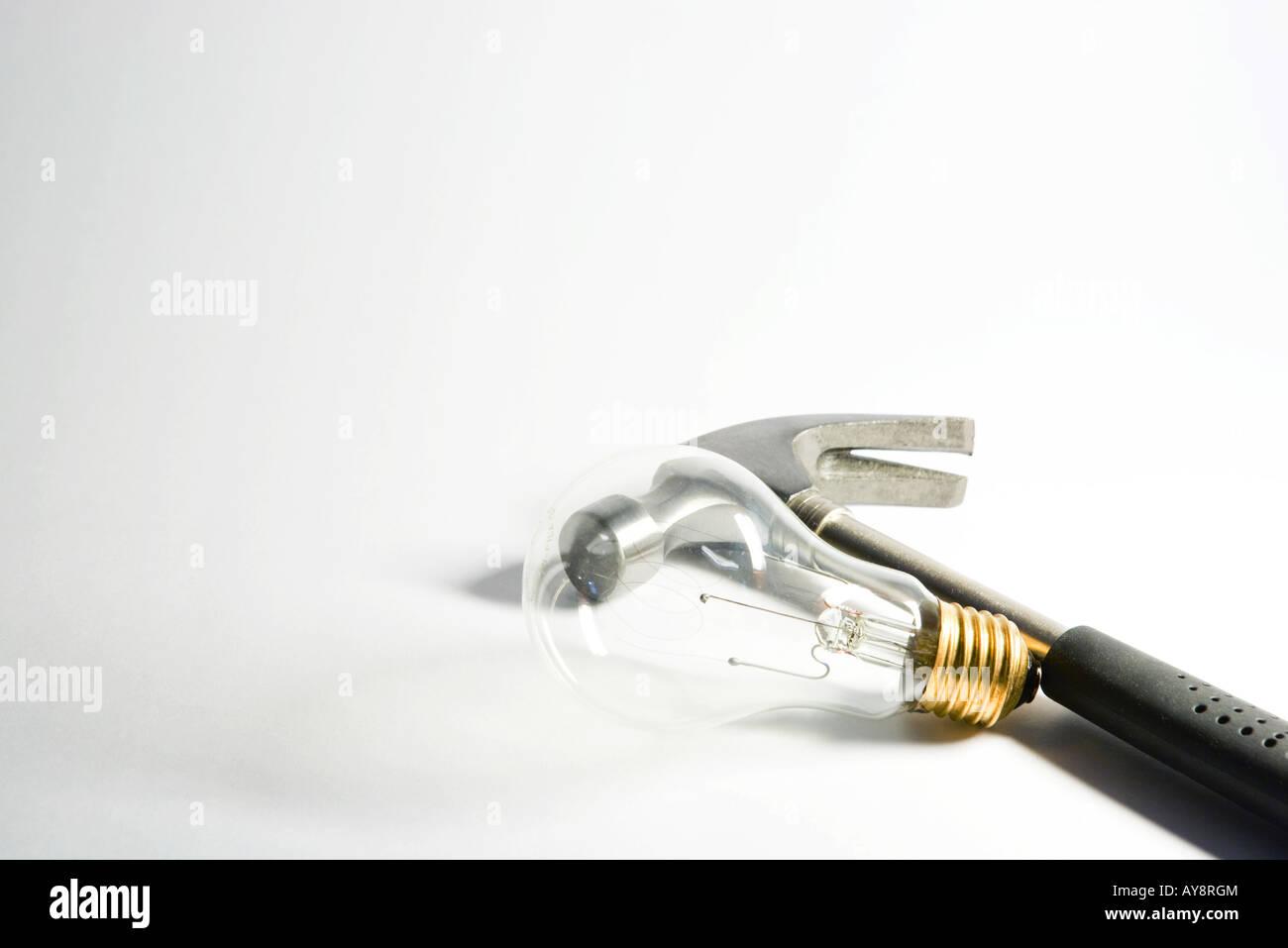 Hammer resting beside light bulb, close-up - Stock Image