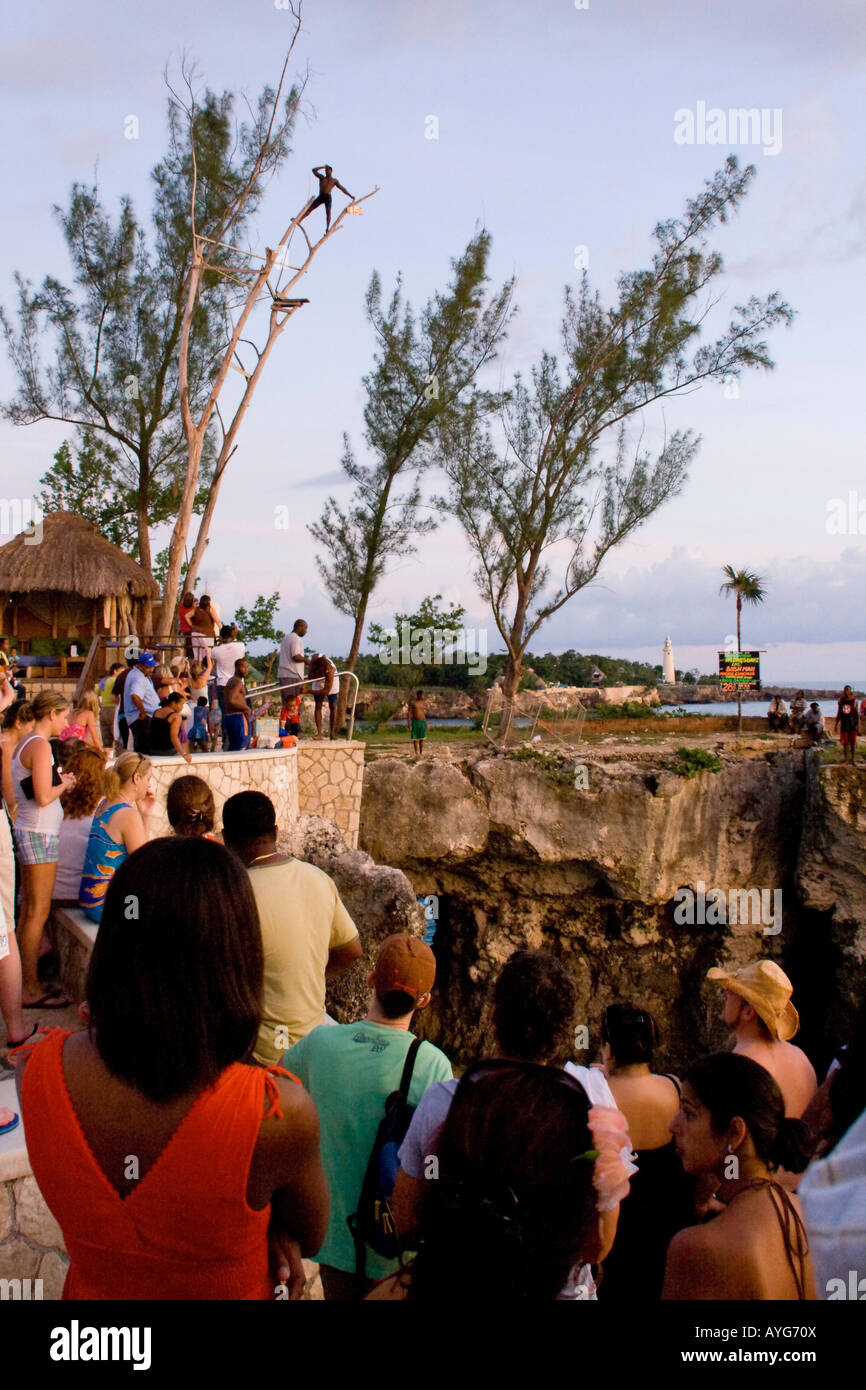 Jamaica Negril Ricks Cafe Cliff Diver jumping from a Tree crowd - Stock Image