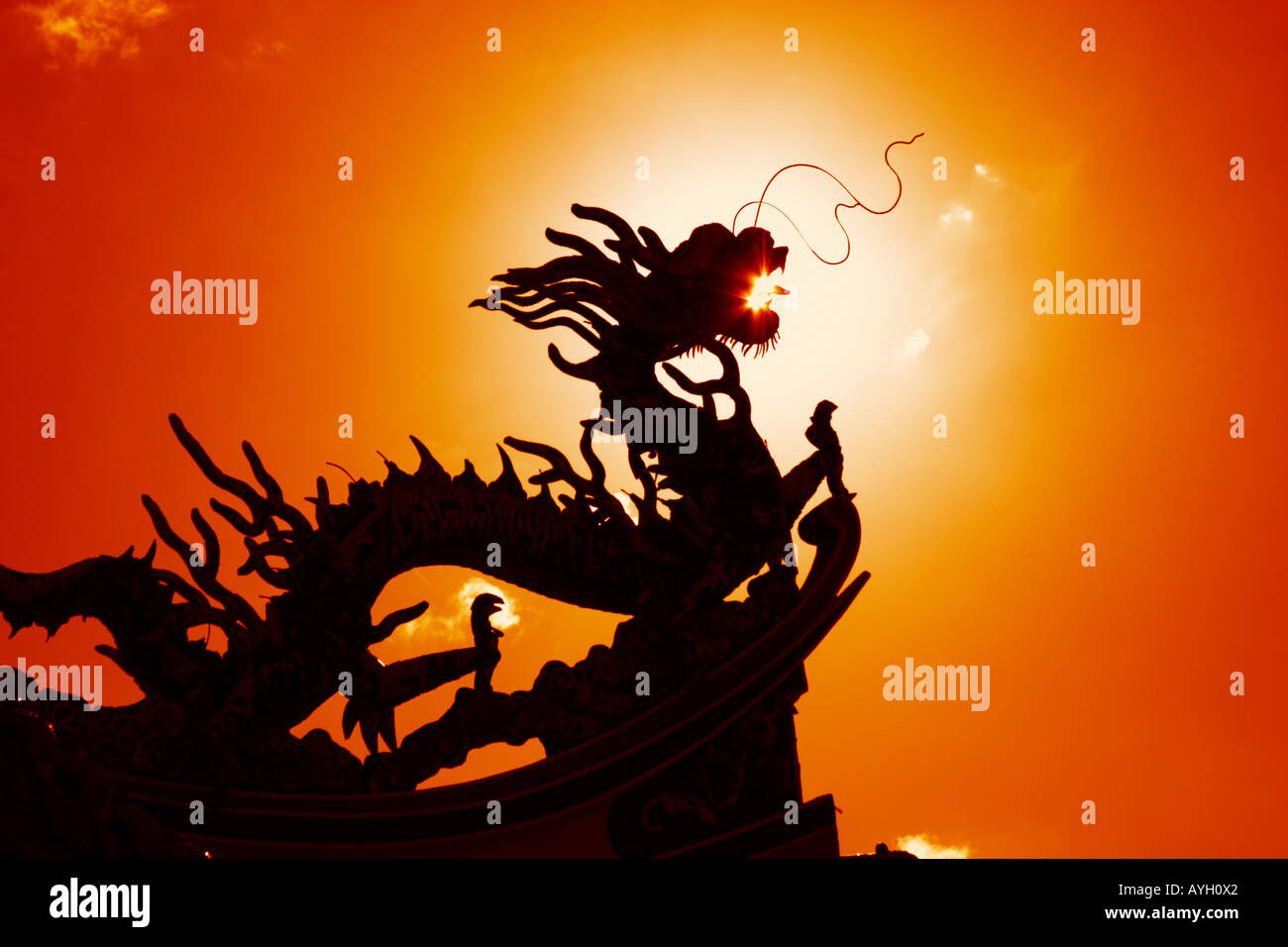 silhoutte of dragon carving on Chinese temple roof with dramatic red bloodlight - Stock Image