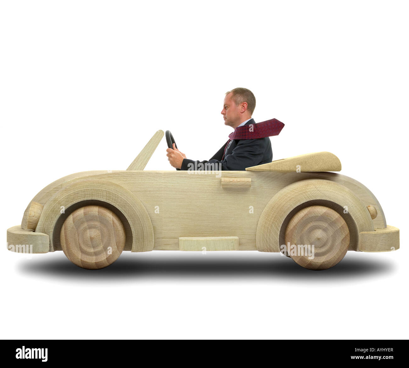 Concept image of a businessman driving to work in his environmentally friendly wooden car - Stock Image