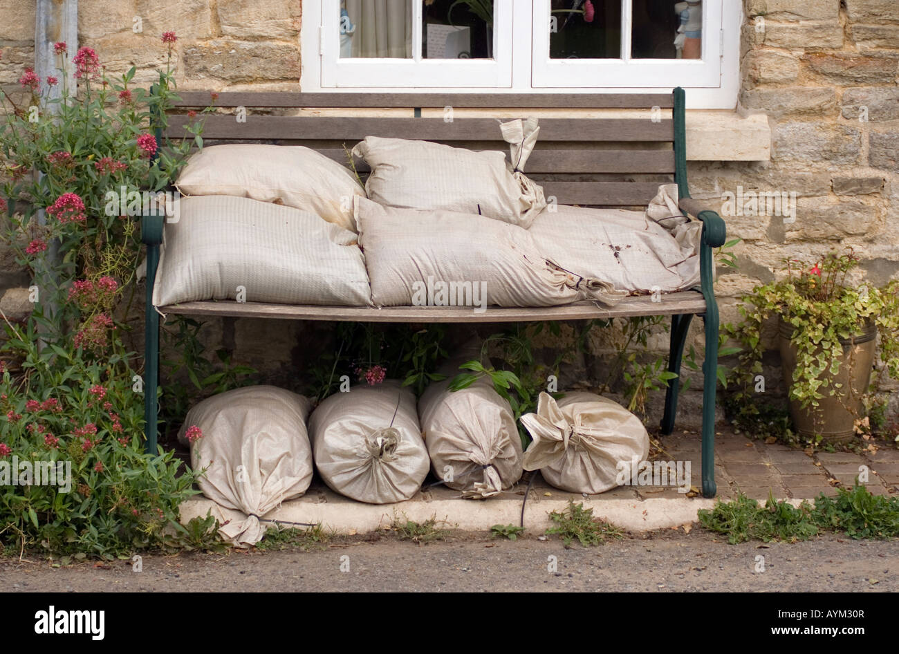 Sandbags ready for use to try and prevent UK flooded in Thrup village in Oxfordshire Oxford Canal river street floods - Stock Image