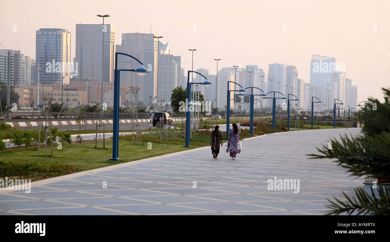 Two arab women walk along the Corniche at dusk, Abu Dhabi city, Abu Dhabi, UAE Stock Photo