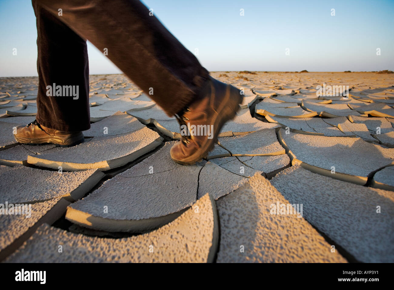 Person with hiking boots walking over cracked dry mud in the Namib desert - Stock Image
