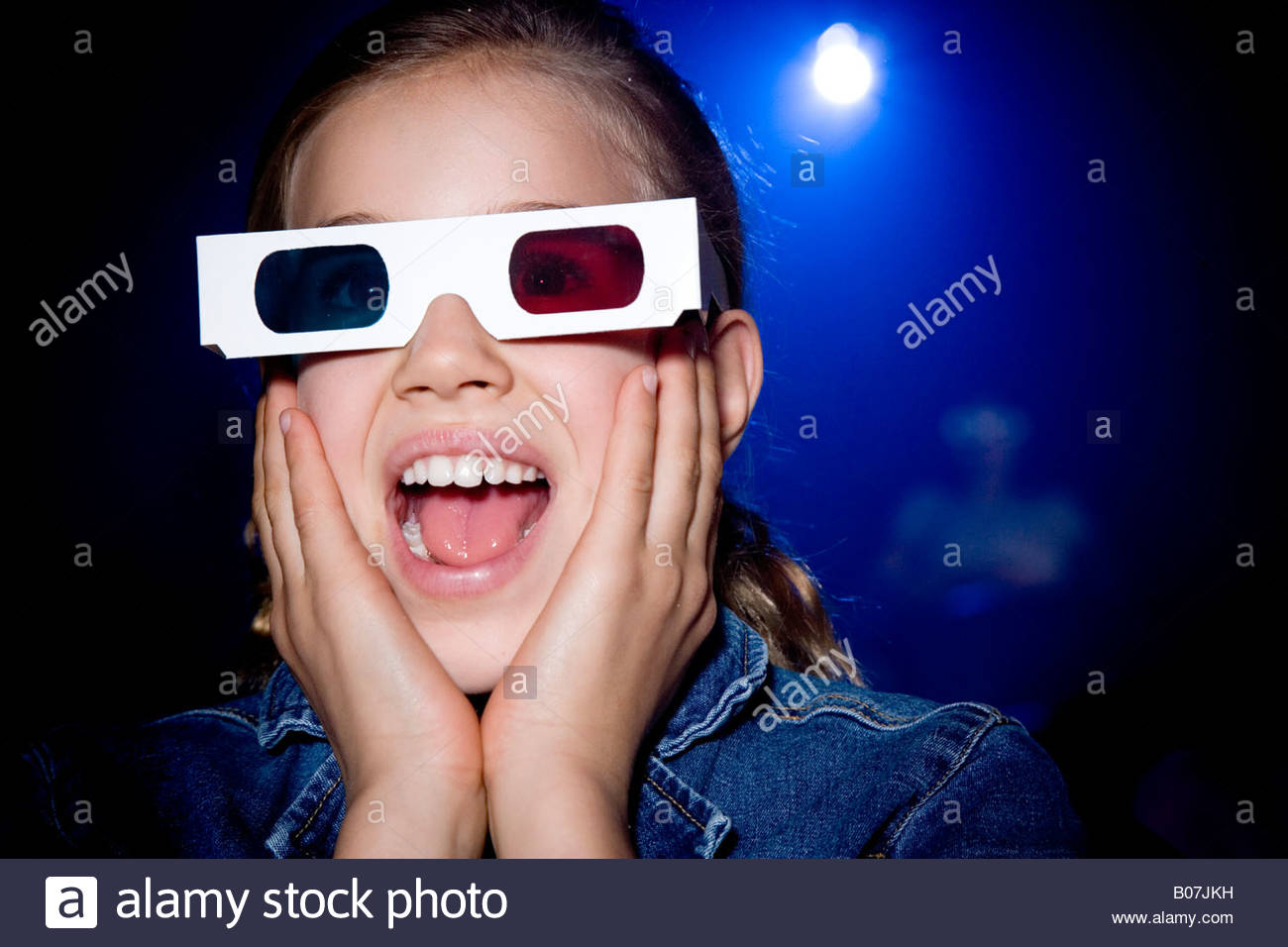Girl at the cinema watching a film through 3-D glasses - Stock Image